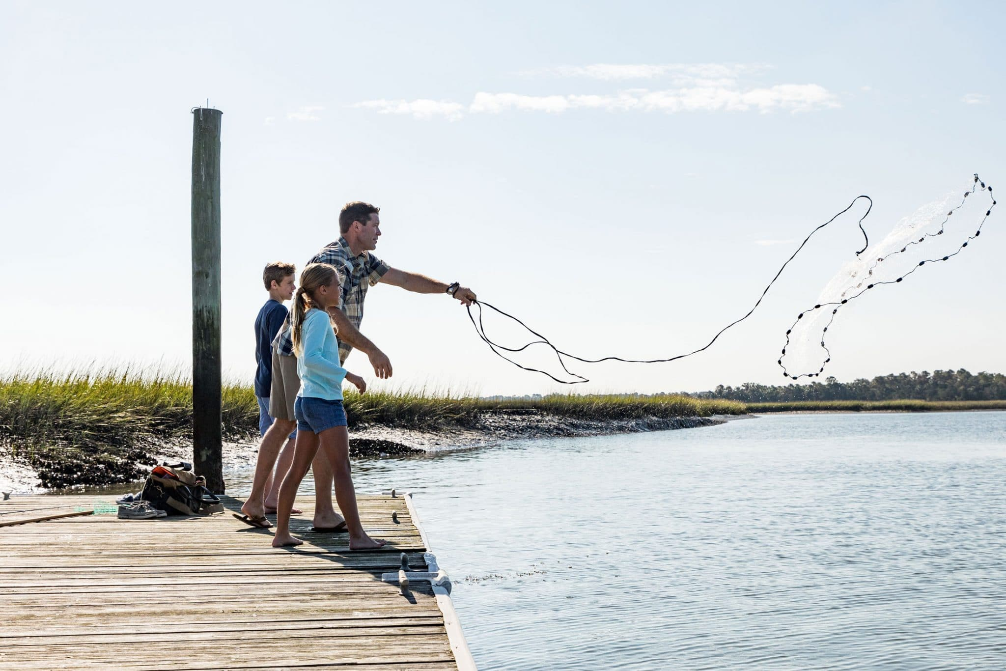father teaching children to throw cast net on kiawah dock