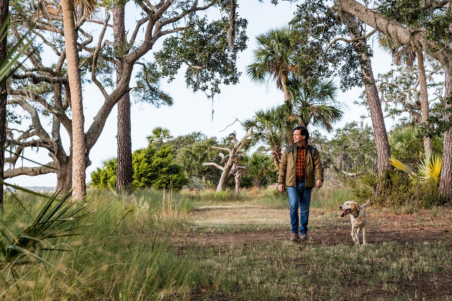 man walking trails with lab at kiawah river development